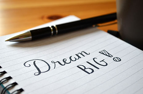 An image of a pad and a pen with the words 'dream big!' written on it.